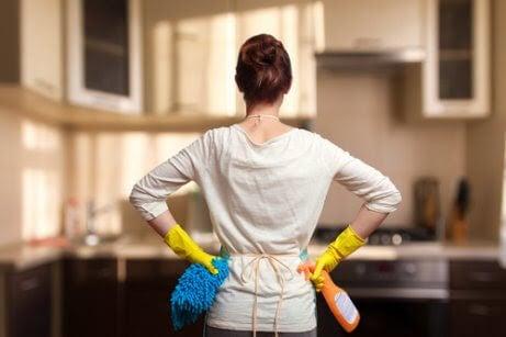 kvinna med städhandskar, sprayflaska och trasa står med ryggen mot kameran och händerna på höfterna