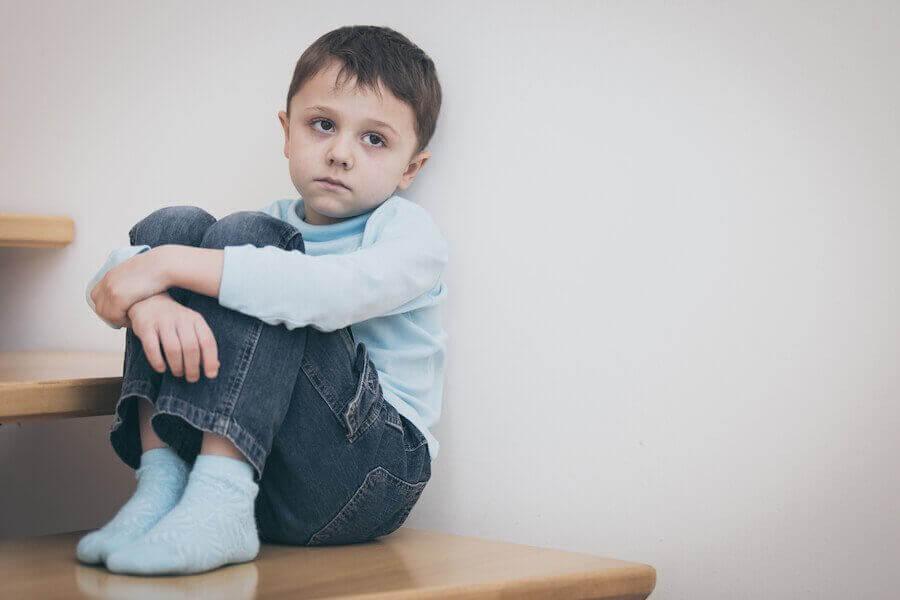 nedstämd pojke sitter på golvet