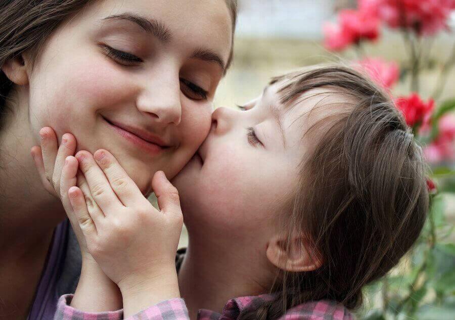 litet barn med downs syndrom kysser kind på äldre syster