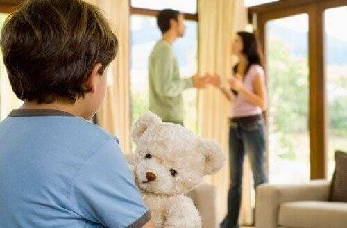 uppfostra barn: mamma och pappa bråkar i bakgrunden, barn med nalle i förgrunden
