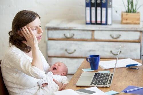 mamma med skrikande baby framför skrivbord