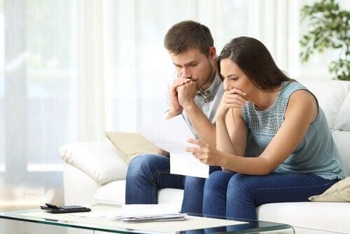 man och kvinna tittar bekymrat på räkningar
