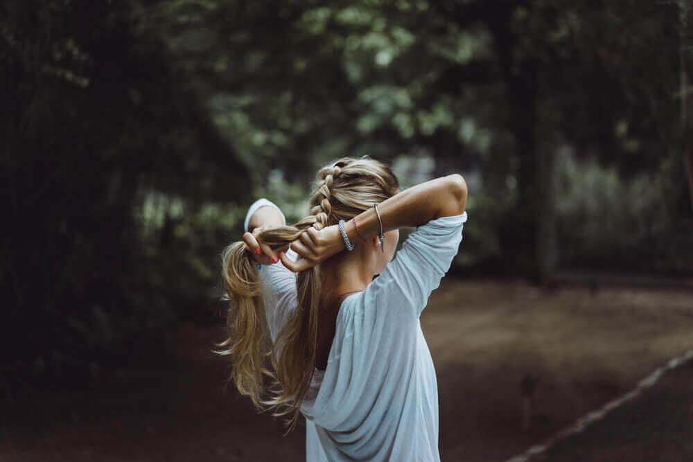 kvinna flätar håret