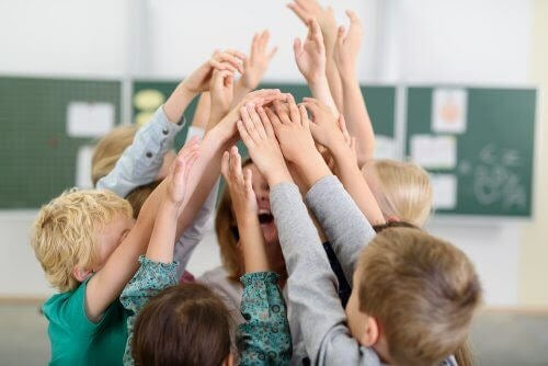 Barn med händerna uppe runt en glad lärare