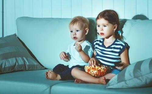 Två små barn i tv-soffa med popcorn