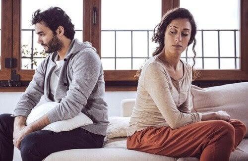 man och kvinna sitter på säng och ser ut att vara ovänner