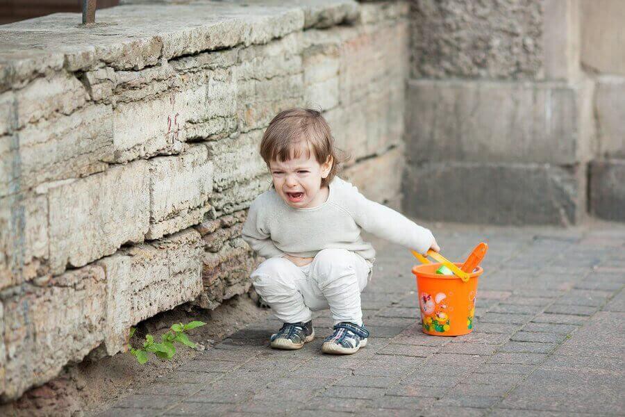 Liten flicka med orange hink sitter och skriker