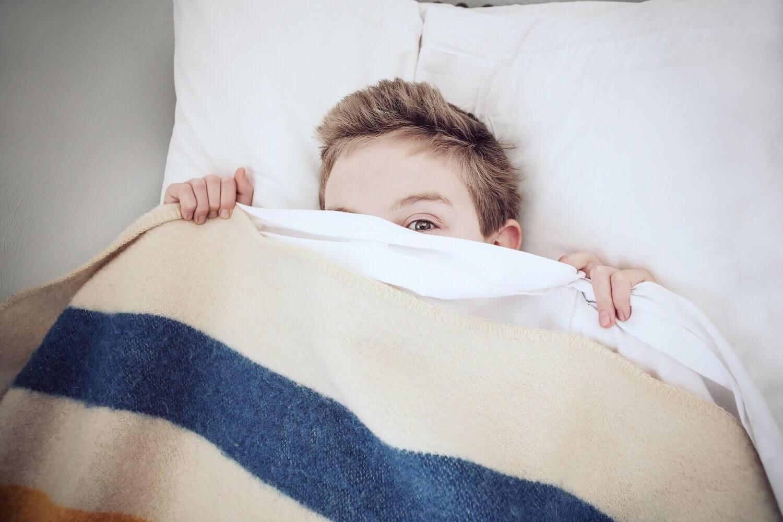 Barn gömmer sig under täcke
