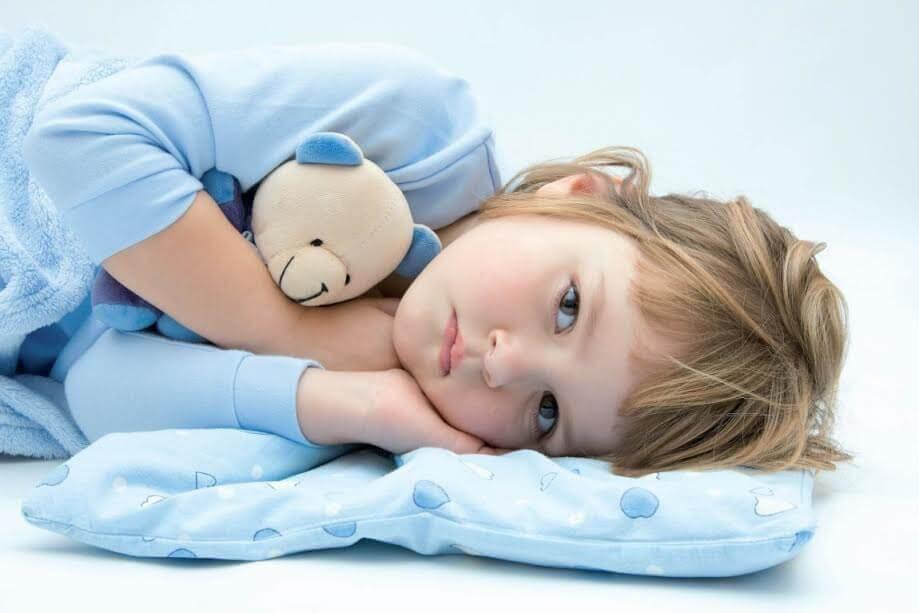 nedstämt barn i säng med nalle