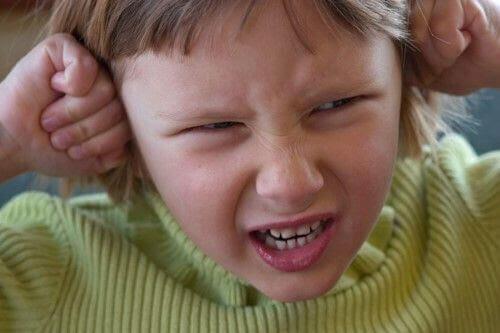 Stressat barn håller för öronen.