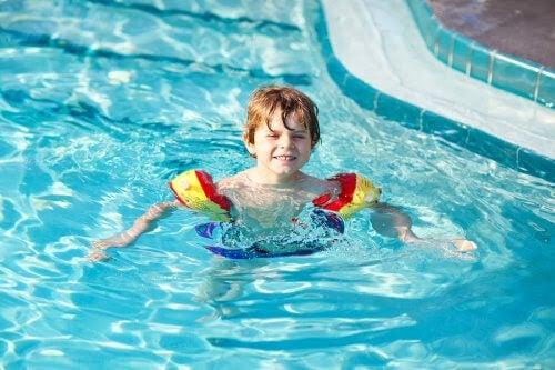 pojke med flytringar i pool