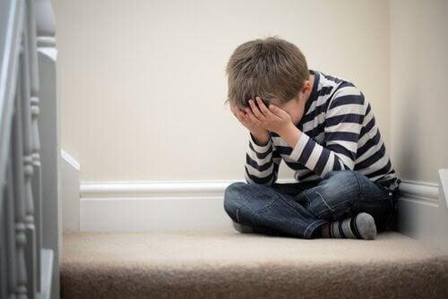 ledsen pojke sitter på golvet