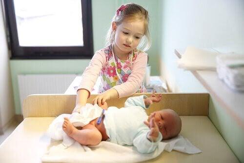 liten storasyster byter blöja på nyfött småsyskon
