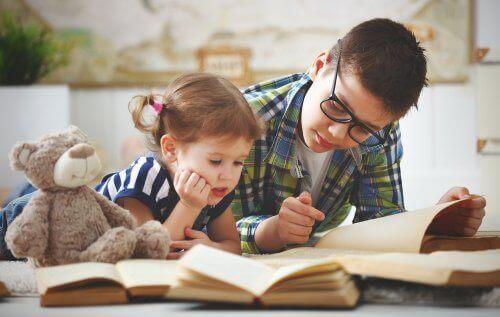 Storebror läser bok för yngre syster.