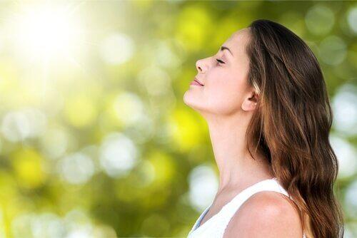 Kvinna fokuserar på andningen och andas in.