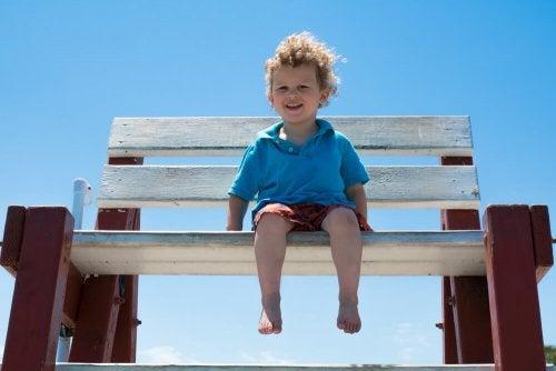 Barfota barn sitter på en stor bänk.