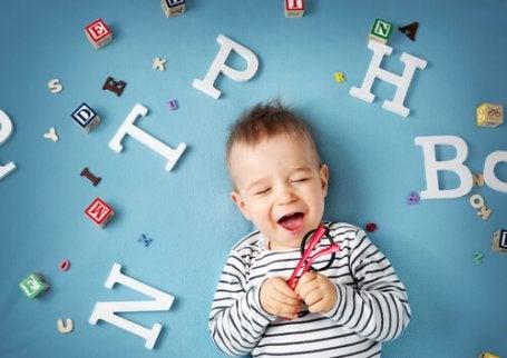 Barn som ligger bland bokstäver och skrattar.