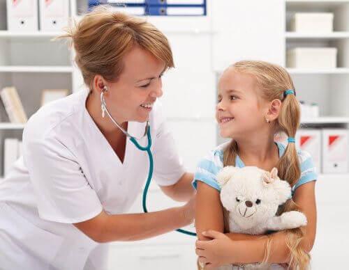 Barn håller i sin nalle under ett besök hos doktorn.
