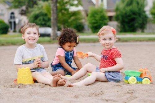 Barn övar på sin sociala kompetens genom lekar i sandlådan.