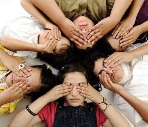 Barn ligger på marken i en cirkel med händerna över ögonen.
