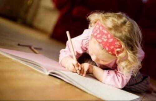 Litet barn använder penna för att skriva i en skrivbok.