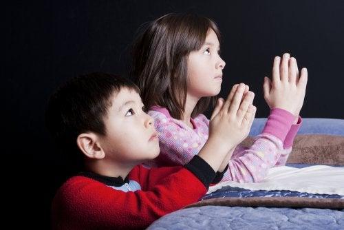 Barn som ber vid sängen.