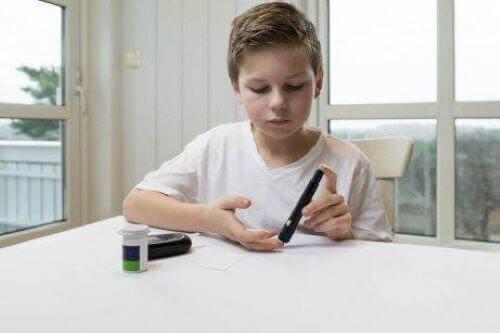Barn sticker sig i fingret för att kolla sitt blodsocker.