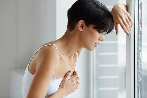 En kvinna har ont i bröstet.