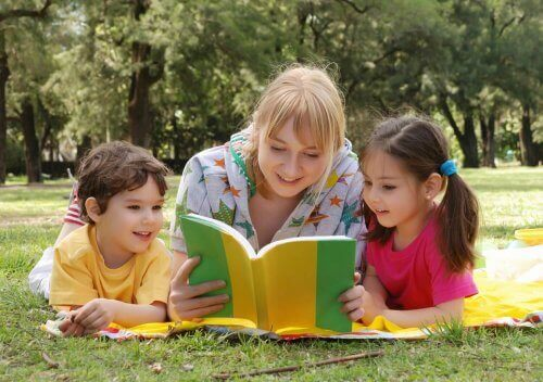 Mamma som läser med sina två barn.