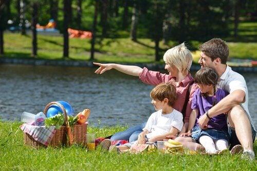 Familj sitter i gräset och njuter av en picknick.
