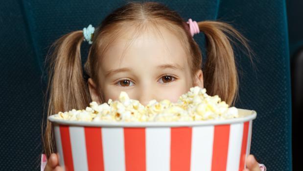 Barn tittar fram bakom popcornbehållaren.