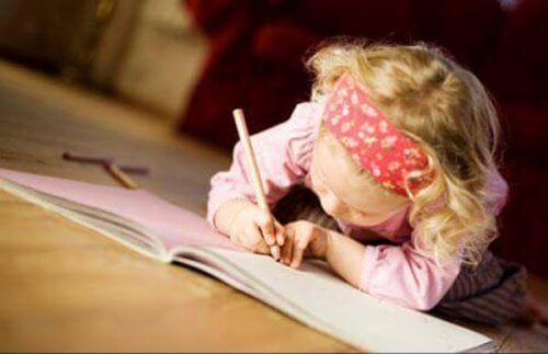Flicka som skriver i bok.
