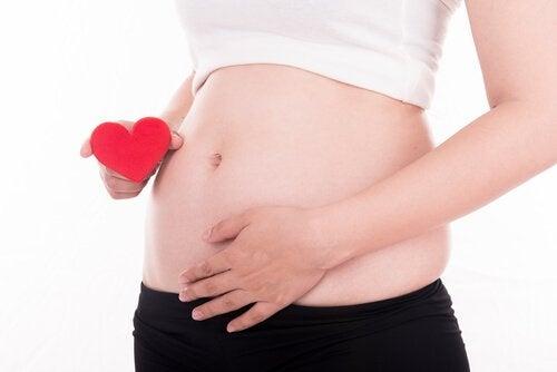 Gravid kvinna i första trimestern med hjärta i handen.