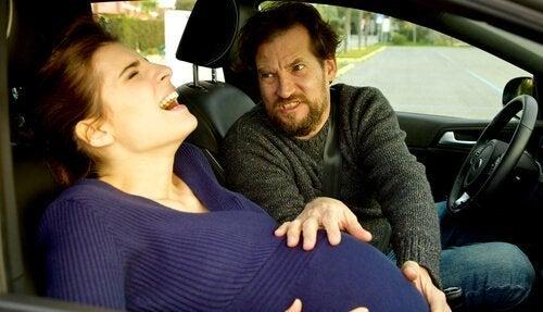 Man tar hand om kvinna med värkar i en bil.