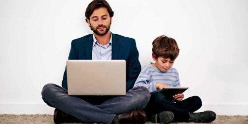 Far och son med varsin dator.