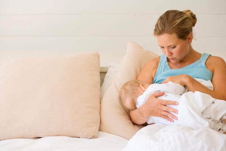 Att vara mamma: Mor som håller om sin bebis.