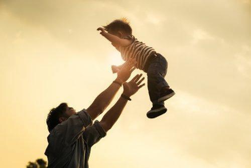 Pappa kastar upp sitt barn i luften.