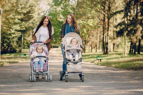 Kvinnor promenerar med barnvagnar.