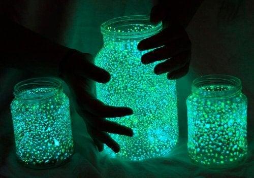Händer som håller i en självlysande lampa.