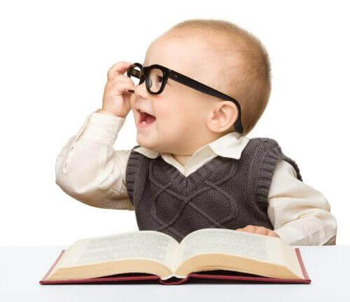 Barn med glasögon läser en bok.