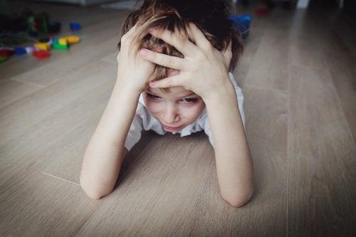 Stressat barn ligger på golvet och håller om sitt huvud.
