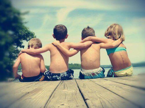 Syskon sitter på bryggan med armarna om varandra.