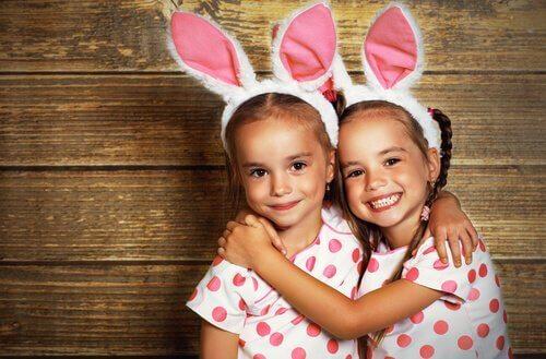 Identiska tvillingar med prickig tröja och kaninöron.