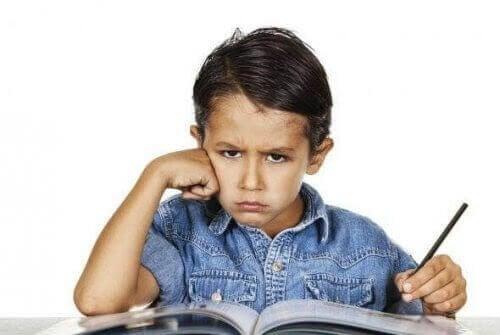 barn vill inte studera: tjurig pojke vid läxbok