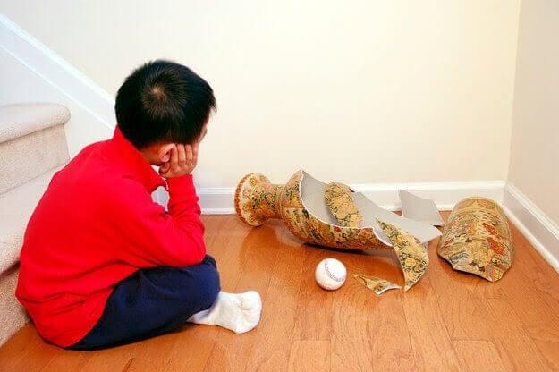 Pojke sitter på golvet bredvid en sönderslagen vas och en boll