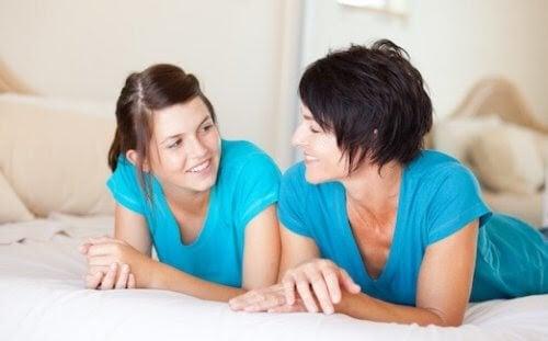 menstruationscykel: mamma och dotter pratar på säng