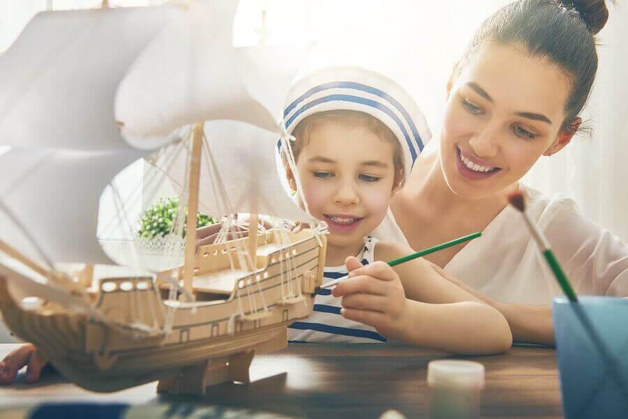 aktiviteter för barn hemma: flicka målar modellskepp och mamma tittar på