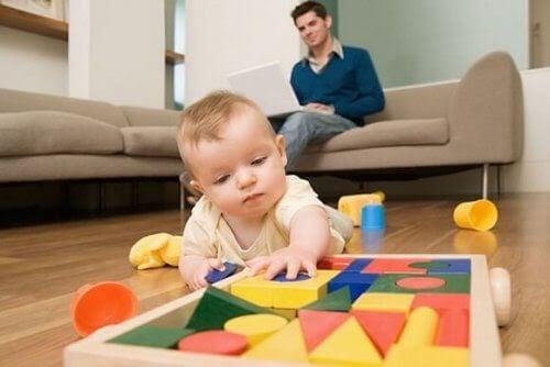 baby leker med klossar, pappa i bakgrunden