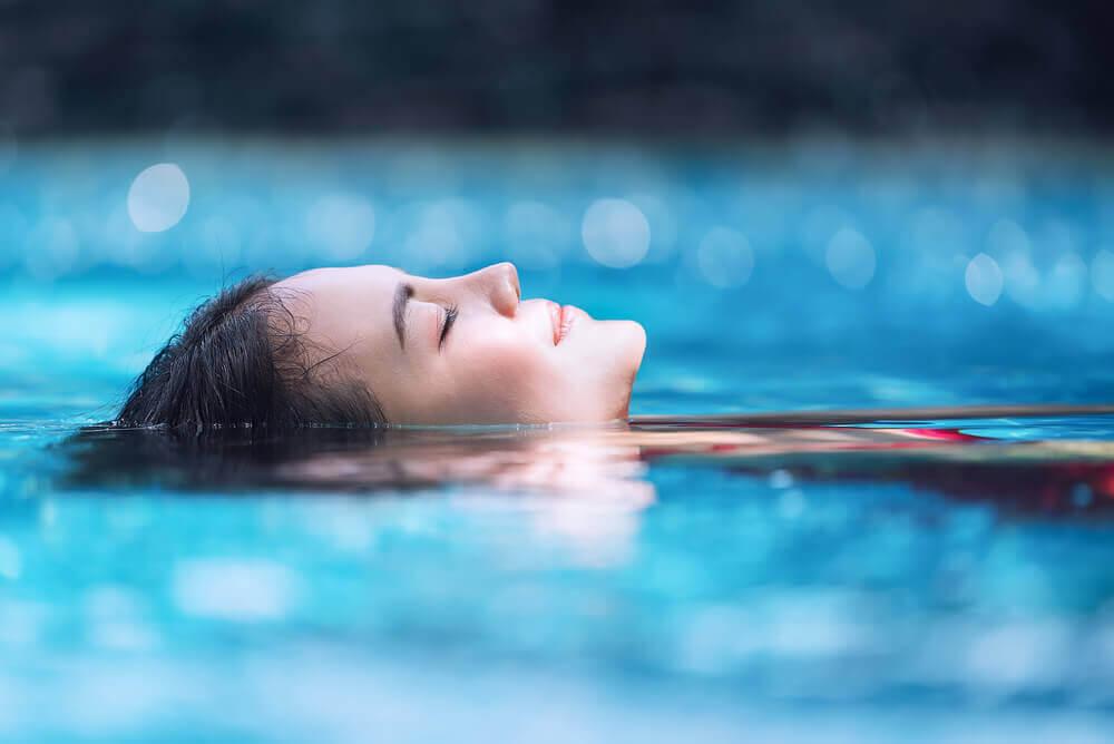Hydroterapi för gravida: avslappnad kvinna flyter i pool