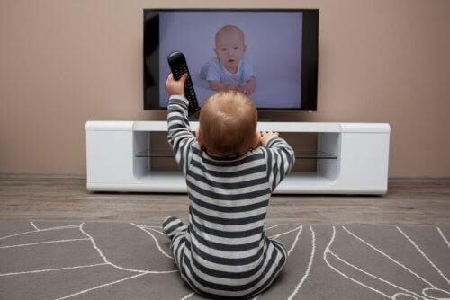 att lära sig språk i barndomen: baby med fjärrkontroll framför tv
